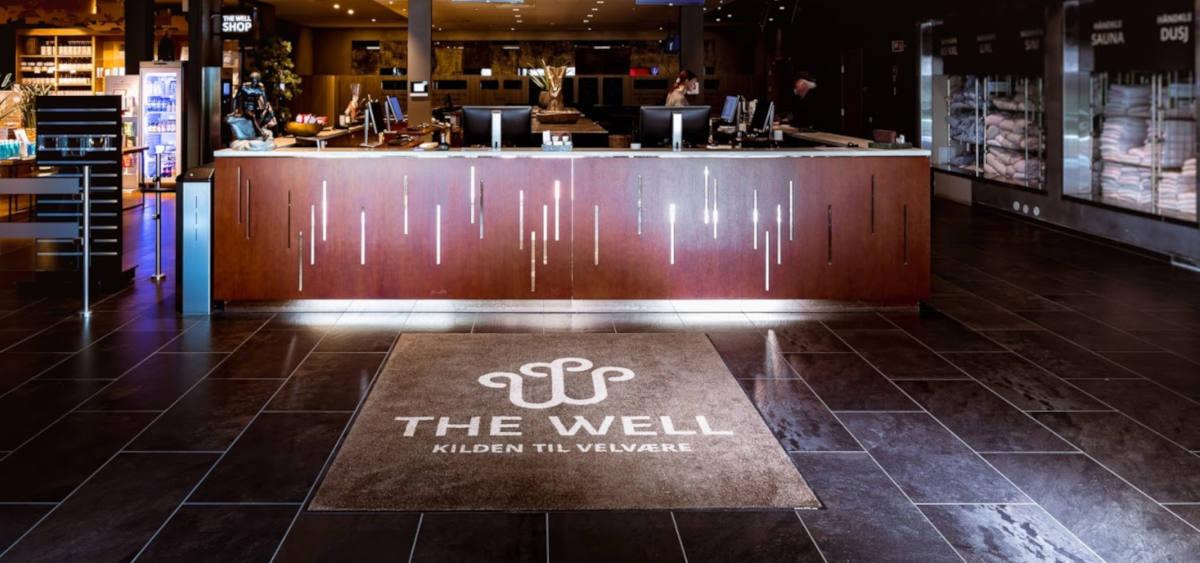En logomatte som ligger foran resepsjonen til The Well