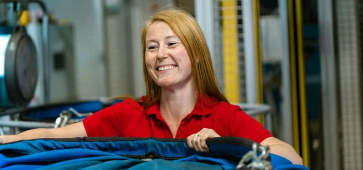 En smilende dame som holder en tralle med arbeidsklær som skal vaskes