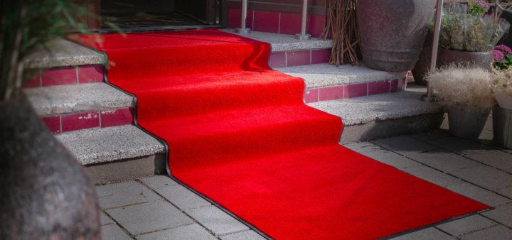 En rød løper ned trapper utenfor en butikk