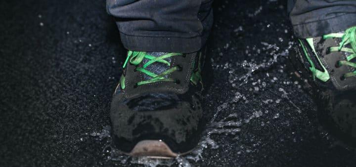 Nærbilde av våte sko som går på en våt matte