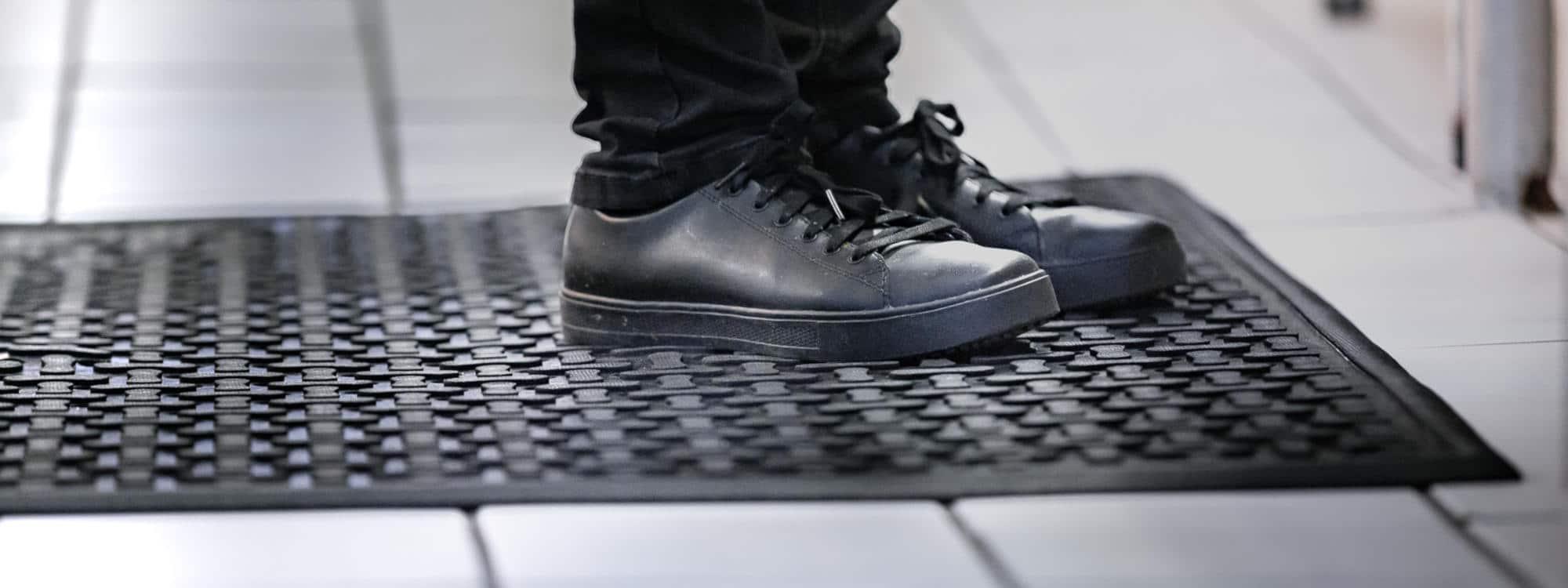 Nærbilde av sko som står på en avlastningsmatte