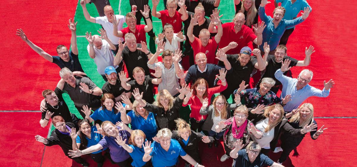 Alle de ansatte i Stil Tekstilservice med armene i være anledning Stil Tekstilservice' 70 års feiring