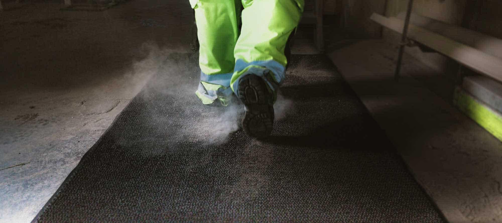 En mann som går på en microluxx matte med støvete sko