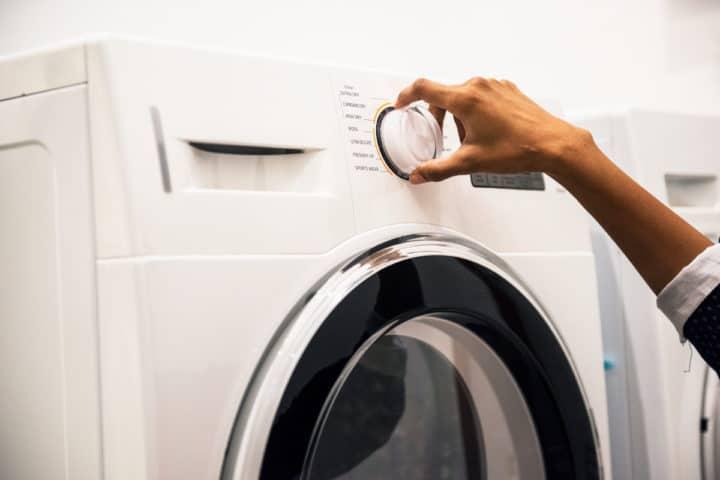 Nærbilde av en hånd som stiller inn vaskemaskinen
