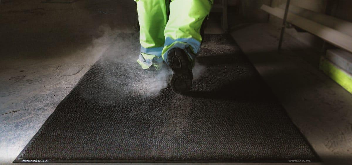 Nærbilde av en person med arbeidsbukse som går på en skitten matte