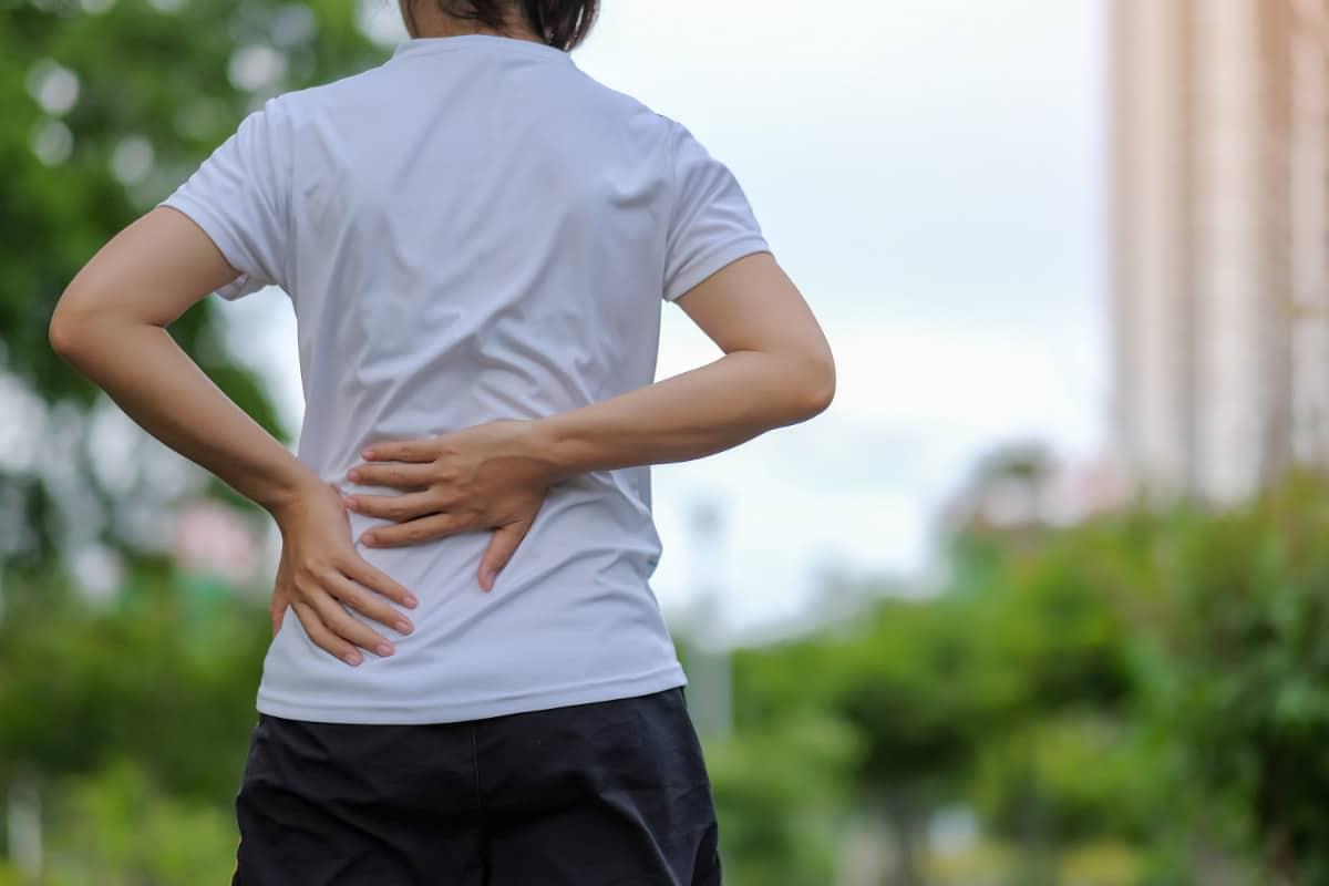 En dame som holder på ryggen sin på grunn av belastningsskader